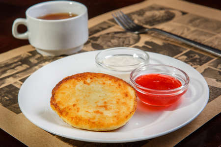 Cheese pancake on a white plate with sour cream and jam, in the background a cup of tea, a fork. Dessert, snack, healthy low-calorie dessert, without sugar Stock Photo
