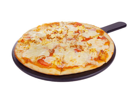 Pizza whole round on a black tray, blackboard, cut into pieces, on a white isolated background. Fast food in a pizzeria, a floury cheese product. Side view
