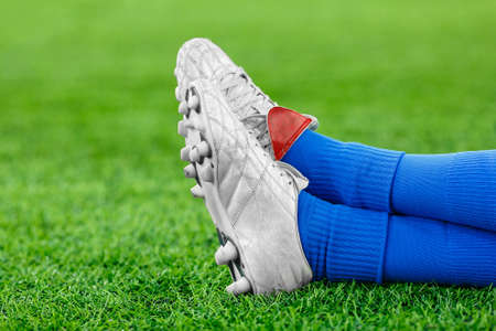 Legs of a player in football, an athlete in blue gaiters and white studded sneakers on a green lawn. Place for the inscription, rest, break, timeout, fatigue, sits, lies. Close up