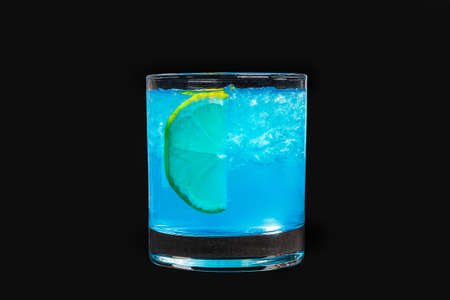 A single-colored transparent cocktail, refreshing shining in a low blue glass with crushed ice frappe and semicircle of a slice of lemon Isolated black background. Side view. Drink for the menu Фото со стока