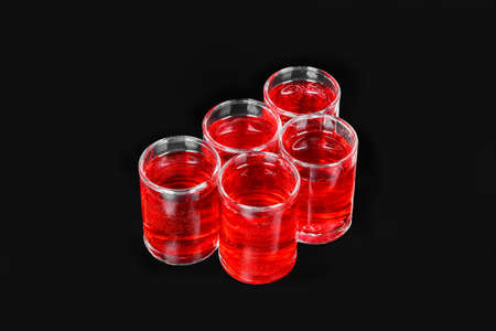 Monochrome transparent cocktails, a set of shots a handful, five servings, with a taste of berries, cherries, strawberries, greiprut, carbonated. Side view from above Isolated black background.