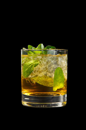 Transparent one-color cocktail in a low glass with crushed ice frappe with mint leaves with melon, pear, apple taste. Side view Isolated black background. Drink for the menu restaurant, bar, cafe Фото со стока