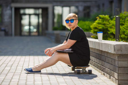 Girl young student plus size in sunglasses sitting on skateboard, in hands phone, laptop, glass of coffee, serious, sad, focused