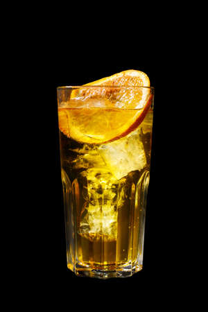 A yellow transparent cocktail, refreshing in a tall glass with ice cubes and lemon slice. Side view Isolated black background. Drink for the menu Banque d'images - 107970035