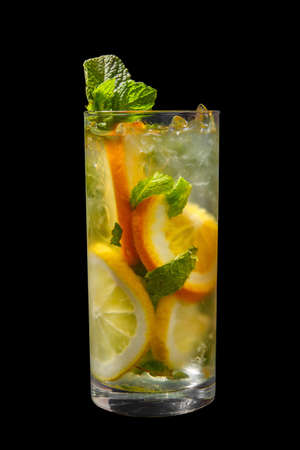 Summer drink with lemon, orange and mint, ice on isolated black background. Direct perspective, cool, refreshing