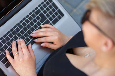Sexually female hands typing on a laptop keyboard close up, outdoors. Freelancer works, looking for a client, fulfilling an order, designer, information technology, job search