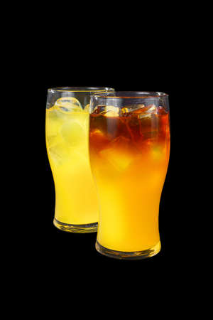 Two yellow multi-colored opaque cocktail in a low glass with ice cubes with melon, pear, apple, berries, fruit, pineapple, orange, Side view, Isolated black background, Drink for the menu