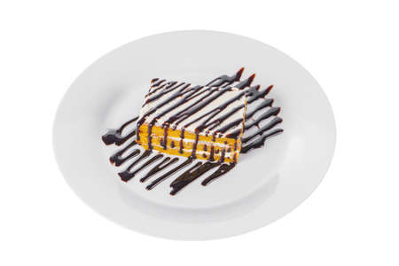 Carrot biscuit pie with cream and chocolate topping, served on a plate isolated white background. Dessert for a menu in a cafe, restaurant, coffee shop side view Imagens