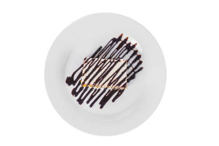 Carrot biscuit pie with cream and chocolate topping, served on a plate isolated white background, pattern red jam. Dessert for a menu in a cafe, restaurant, coffee shop, view from above Imagens