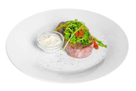 Bistecca di manzo, agnello con rucola, pomodori secchi e tartaro, panna acida, maionese, salsa bianca su un piatto, sfondo bianco isolato, vista laterale