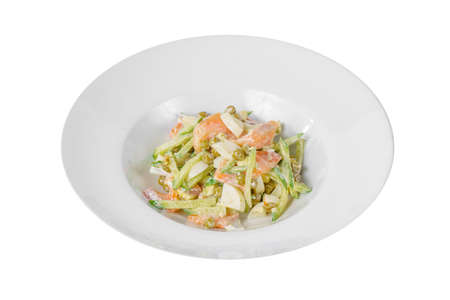 Russian salad with fish salmon, cucumber, peas, eggs, mayonnaise on plate, white isolated background, side view