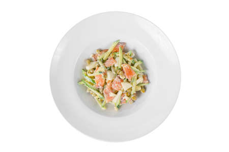 Russian salad with fish salmon, cucumber, peas, eggs, mayonnaise on plate, white isolated background, view from above 스톡 콘텐츠 - 124995206