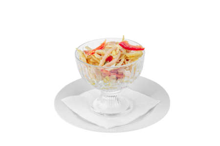 Salad with red Bulgarian pepper, chicken or squid meat, ham, egg, cabbage, potatoes, spicy on plate in tall bowl, white isolated background, side view