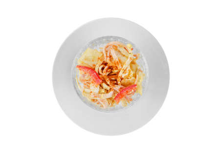 Salad with red Bulgarian pepper, chicken or squid meat, ham, egg, cabbage, potatoes, spicy on plate, white isolated background, view from above