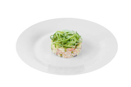 Russian salad with straw from cucumber, peas, carrots, potatoes on plate, white isolated background, side view