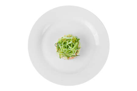 Russian salad with straw from cucumber, peas, carrots, potatoes on plate, white isolated background, view from above