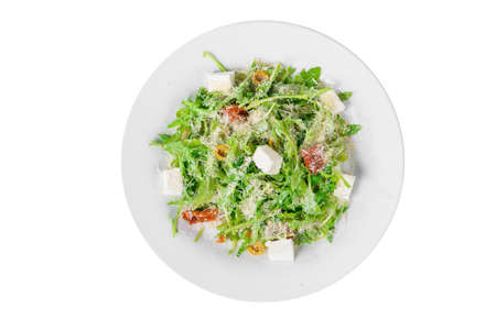 Salad with with arugula, feta, dried tomatoes, olives and grated cheese on plate, white isolated background, view from above Banco de Imagens