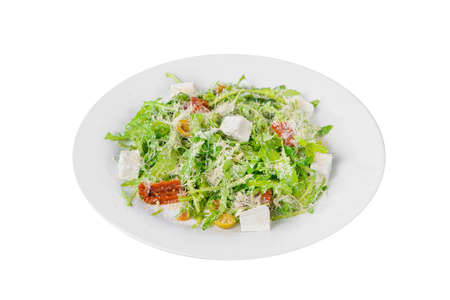 Salad with with arugula, feta, dried tomatoes, olives and grated cheese on plate, white isolated background, side view
