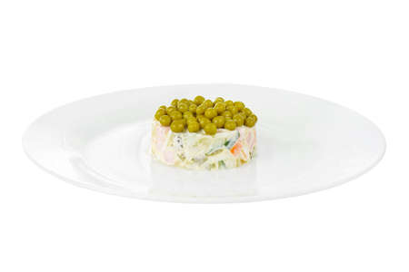 Russian salad with peas, eggs, cucumbers, carrots, ham, sausage, potatoes on plate, side view white isolated background