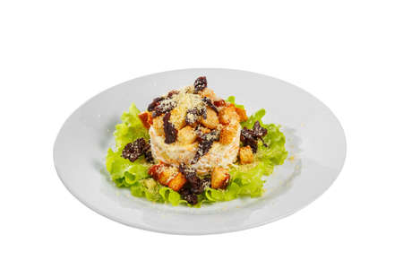 Salad with bread crumbs and prunes on lettuce, carrots, potatoes and mayonnaise on plate, white isolated background, side view Imagens