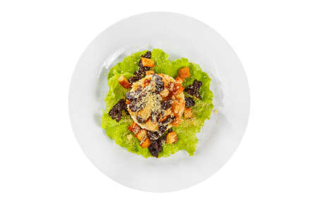 Salad with bread crumbs and prunes on lettuce, carrots, potatoes and mayonnaise on plate, white isolated background, view from above