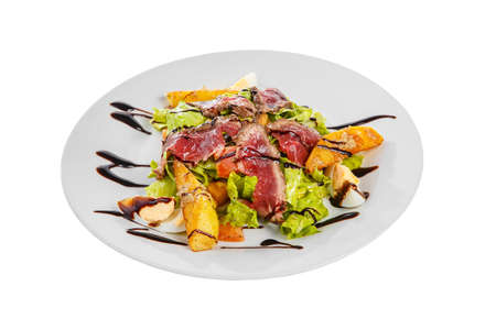 Salad with roast beef with fried potatoes, eggs, lettuce, tomatoes balsamic vinegar, sauce on plate, white isolated background, side view Imagens