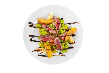Salad with roast beef with fried potatoes, eggs, lettuce, tomatoes balsamic vinegar, sauce on plate, white isolated background, view from above 스톡 콘텐츠 - 124995347