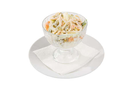 Russian salad with ham and squid, cucumber, peas, eggs, mayonnaise on plate in a tall bowl, white isolated background, side view