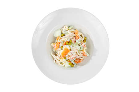 Russian salad with fish salmon, cucumber, peas, eggs, mayonnaise on plate, white isolated background, view from above