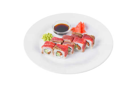 Sushi, rolls, uramaki with bacon, cucumber, cheese, meat and teriyaki sauce, marinated ginger and wasabi, white isolated background, side view Banco de Imagens