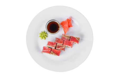 Sushi, rolls, uramaki with bacon, meat and teriyaki sauce, raw seafood, marinated ginger and wasabi, white isolated background, view from above Stock Photo