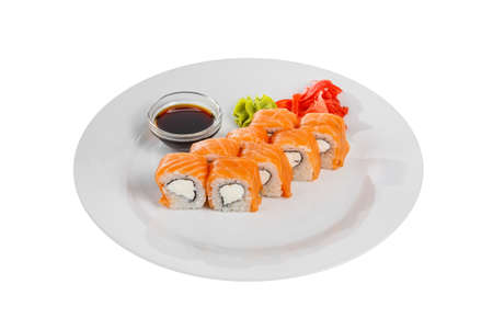 Sushi, rolls, uramaki, philadelphia with salmon, cheese, raw seafood, soy sauce, marinated ginger and wasabi, white isolated background side view Banco de Imagens