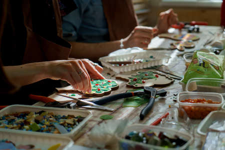 The artist maker mosaic in a wooden harvesting. Two female hands closeup collect mosaic of colored stones. Human activity to workplace sunray Reklamní fotografie