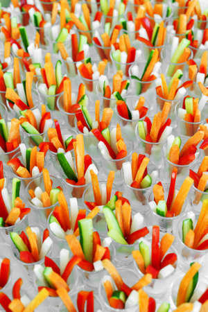 Celebration catering, small portions of colored vegetables in glass, side view, large amounts, daylight