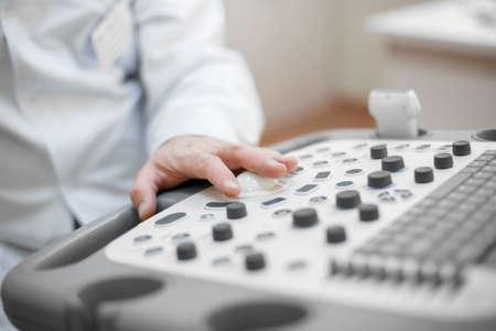 Arzt richtet ein Ultraschallgerät ein, Hand hautnah. Analyse, Diagnose des Krankheitszustandes durch Ultraschalluntersuchungen