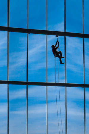 Industrial climber hangs from ropes inside shopping center or exhibition hall building against the blue sky, plenty of free space to sign Stock Photo - 122915611