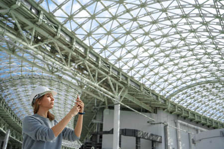A young girl in a helmet in a large room with a glass roof takes pictures on the phone. A serious expert, a woman inspects the object