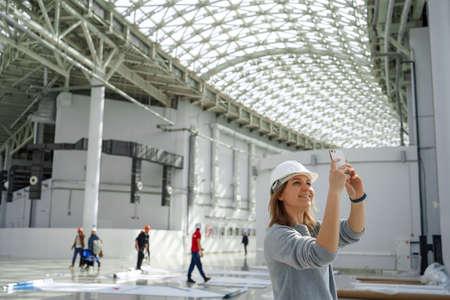 Jong meisje in een helm maakt foto's aan de telefoon, op de achtergrond de arbeiders, een excursie naar de bouwplaats, een ingenieur is tevreden