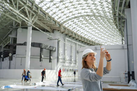 Young girl in a helmet takes pictures on the phone, in the background the workers, an excursion to the construction site, an engineer is satisfied Stockfoto