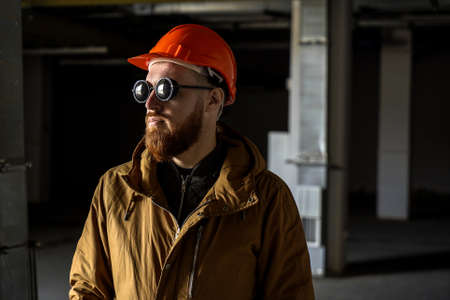 Adult man with a red beard in a helmet and round sunglasses in a dark room, looks away, horizontal frame, medium plan, conceptually