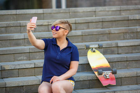 stylish girl of plus size, fashionable haircut in mirror glasses, sitting on the steps, taking pictures of herself with a smartphone, longboard beside