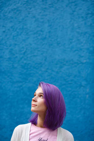 beautiful bright girl with purple hair on a blue background looking up and to the side, free space, blue eyes, hope and optimism