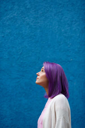 beautiful bright girl with purple hair on a blue background looking up and to the side, free space, in profile, hope and optimism