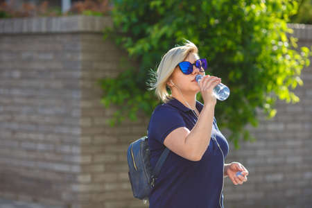 stylish girl plus size in blue t-shirt and sunglasses drinks water from a bottle, listens to headphones, against a background of a wall and wood
