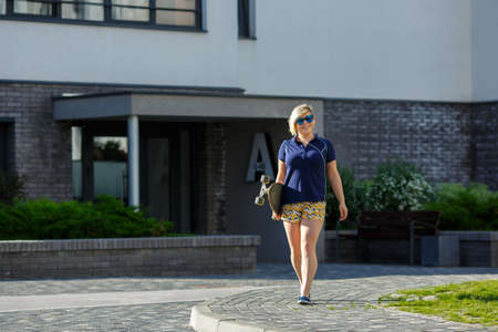 stylish girl plus size in blue t-shirt and shorts and sunglasses with a longboard in her hands goes ahead, smiles, listens to headphones