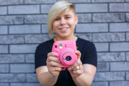 stylish large girl in a black t-shirt smiles and takes pictures on a pink camera against the wall