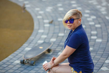 stylish girl plus size, fashionable haircut in mirror glasses, headphones, smiling, holding a smartphone in her hands, sitting on the steps, longboard 스톡 콘텐츠