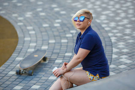 stylish girl plus size, fashionable haircut in mirror glasses, headphones, smiling, holding a smartphone in her hands, sitting on the steps, longboard Stock Photo