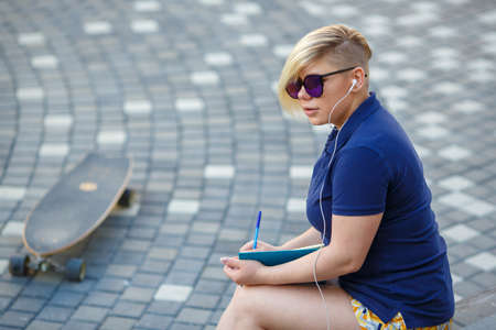 stylish girl plus size, fashionable haircut in mirror glasses, headphones, sitting outdoors, writes in a notebook, longboard