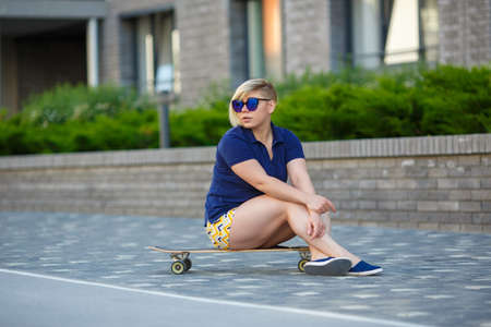 stylish girl of plus sizes, fashionable haircut in mirror glasses, sitting on a longboard against the background of the building 스톡 콘텐츠
